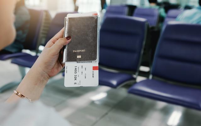 Woman hand holding passport and flight ticket